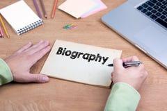 Hand het schrijven Biografie Bureau met laptop en een kantoorbehoeften Royalty-vrije Stock Afbeelding