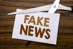 Hand het schrijven de inspiratie die van de teksttitel Vals Nieuws tonen Bedrijfsdieconcept voor Hoax Journalistiek op nota, hout stock fotografie