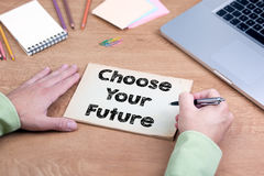 Hand het schrijven kiest Uw Toekomst Bureau met laptop en s stock fotografie