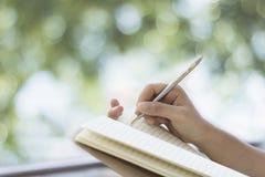 Hand het schrijven van vrouwen op notadocument op balkon en groene bokeh van boomachtergrond Royalty-vrije Stock Afbeelding
