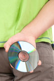 Hand hides optical disk behind bac. K on white background Royalty Free Stock Photo