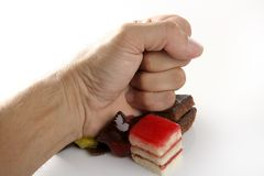 Hand hits little cakes with closed fist Stock Photo