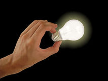 Hand hloding a light bulb, isolated dark Royalty Free Stock Photo