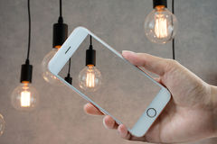 Hand hloding smart phone at bulb. Hand hloding smart phone at ligh bulb Royalty Free Stock Images