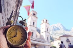 Hand hold alarm clock with city landscaps of Kotor at Montenego royalty free stock image