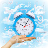 Hand hold alarm clock with figures Royalty Free Stock Photography