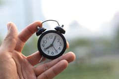 Hand hold alarm clock in outdoor backgound royalty free stock image