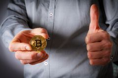 Hand hold bitcoin. And next hand shows thumb up Royalty Free Stock Photo