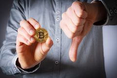 Hand hold bitcoin. And next hand shows thumb down Royalty Free Stock Photos