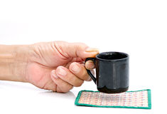 Hand hold with black cup on the white table Royalty Free Stock Photos