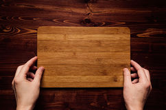 Hand hold blank bamboo sign board on brown vintage wood plank, top view. Royalty Free Stock Photography