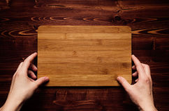 Hand hold blank bamboo sign board on brown vintage wood plank, top view. Royalty Free Stock Photos