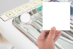 Hand hold blank card and dental clinic equipment on metal plate Royalty Free Stock Photo