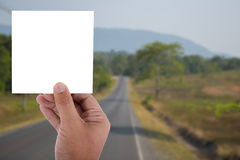 Hand hold blank paper over blur image of tree and road. In background Royalty Free Stock Photo