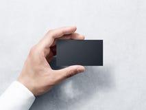 Hand hold blank plain black business card design mockup. Royalty Free Stock Photos