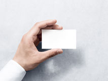 Hand hold blank plain white business card design mockup. Clear calling card mock up template holding arm. Visit pasteboard paper surface display front. Check Stock Photos