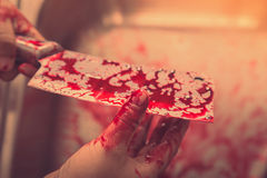 Hand hold bloody knife in a steel shell for halloween ( Filtered Royalty Free Stock Image