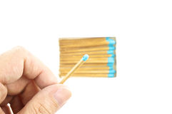 Hand hold blue matchstick for lit and box isolated Royalty Free Stock Images