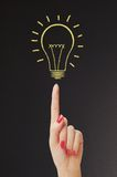 Hand hold bright light bulb with board Royalty Free Stock Photography