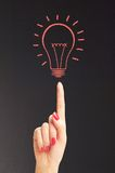 Hand hold bright light bulb with chalk board Stock Photo