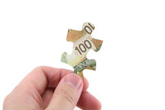 Hand hold canadian dollar puzzle Stock Photography
