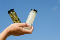 Hand hold caper garlic jar on blue sky background Stock Images