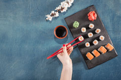 Hand hold chopsticks on sushi with sauce, wasabi, sakura, ginger Royalty Free Stock Images