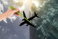 Hand hold a chopsticks tong a plane on a building background - A Stock Photo