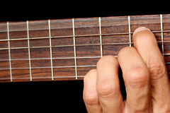 Hand, hold a chord on the guitar fretboard, vibrating string Stock Image