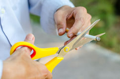 Hand hold cigarette being cut with scissors Stock Photography