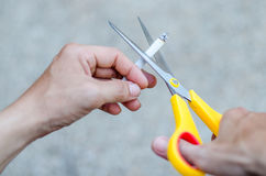 A hand hold cigarette being cut with scissors Royalty Free Stock Images