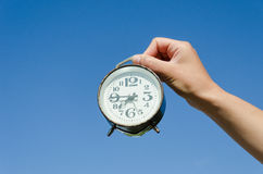Hand hold clock with big numeral on sky background Stock Photo