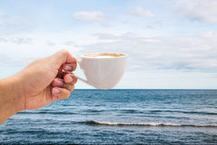 hand hold coffee cup on ocean Royalty Free Stock Photo