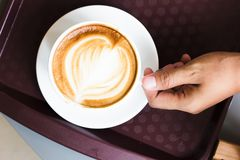 Hand hold coffee latte in white cup from top view. Royalty Free Stock Photo