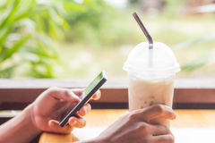 Hand hold coffee and use smart phone mobile Stock Image