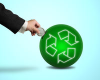 Hand hold coin insert into ball with recycling symbol. In blue background Royalty Free Stock Photo