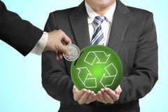 Hand hold coin insert into ball with recycling symbol. Isolated in green background Royalty Free Stock Image