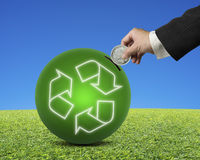 Hand hold coin insert into ball with recyling symbol Royalty Free Stock Photos