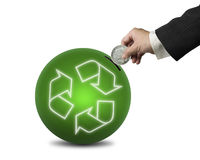 Hand hold coin insert into ball with recyling symbol , isolated Royalty Free Stock Photography