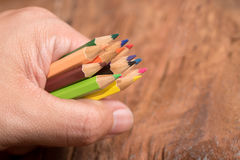 Hand hold colorful pencils on wood table Royalty Free Stock Image