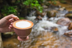 Hand hold a cup of cappuccino at rill. Stock Photos