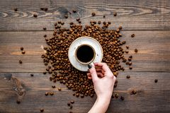 Hand hold cup of freshly brewed full-bodied coffee on dark wooden table top view. Coffee background. Stock Images
