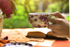 Hand hold cup of tea with lilac bouquet in vase and book. On summer flower garden background Stock Photos