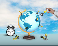 Hand hold dollar chess on terrestrial globe with clock. Hand hold dollar chess on terrestrial globe with alarm clock and sky background Stock Images