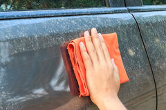 Hand hold a fabric wiping dirty car. stock image