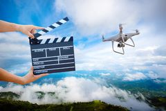 Hand hold Film Slate with drone copter. Man hands holding movie clapper.Film director concept. UAV drone copter flying for image catch motion in interview or stock images