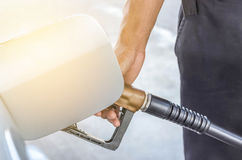 Hand hold fuel nozzle refueling gas pump in service station Royalty Free Stock Photography