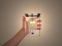 Hand hold glass jar with bulb inside isolated Royalty Free Stock Photo
