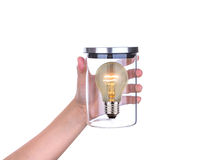 Hand hold glass jar with bulb inside isolated Stock Images