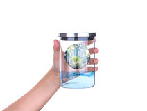 Hand hold glass jar with earth and water inside isolated Royalty Free Stock Photo